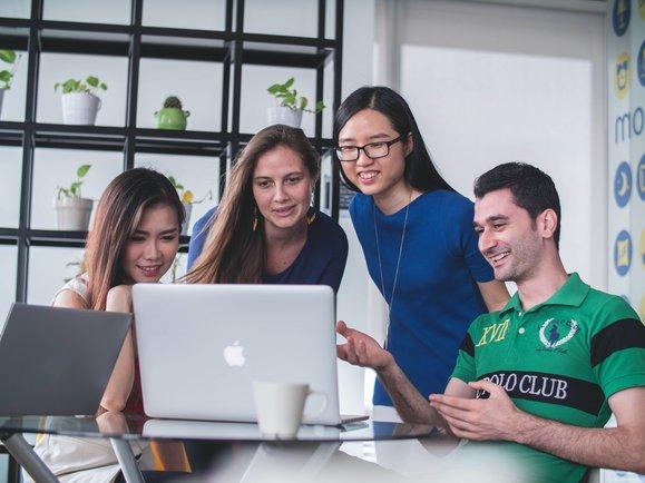 Gruppe von Gründern schauen gemeinsam auf den Laptop