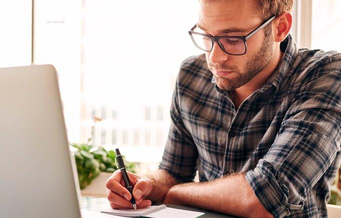 Junger Mann arbeitet an einem Laptop