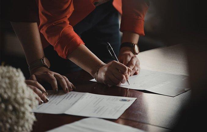 [Translate to English:] Junge Frau unterzeichnet ein Dokument