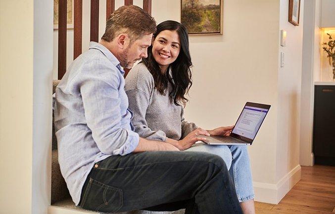 Zwei Personen schauen auf einen Laptop