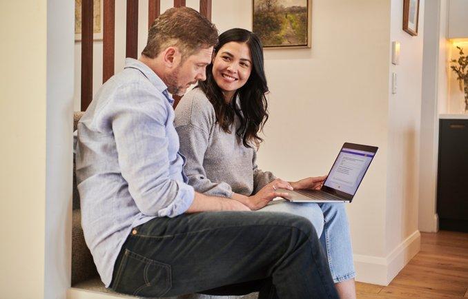 Zwei Menschen schauen auf einen Laptop