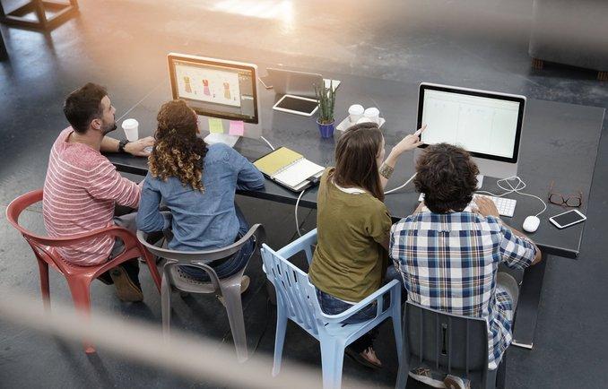 Vier Personen recherchieren an einem Computer