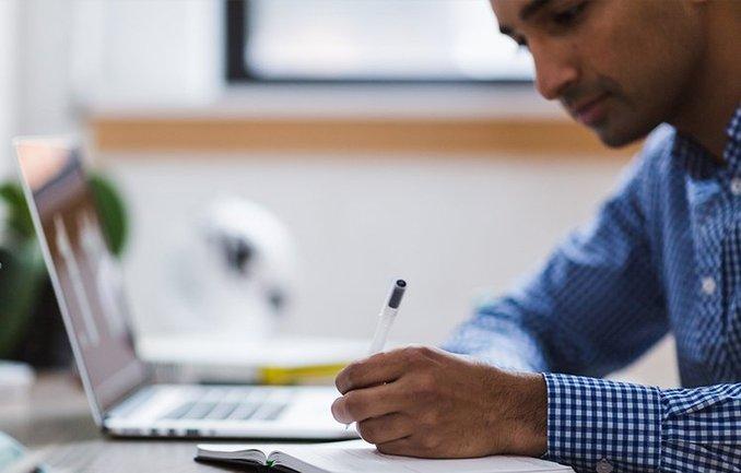 Junger Mann bei der Arbeit an einem Laptop